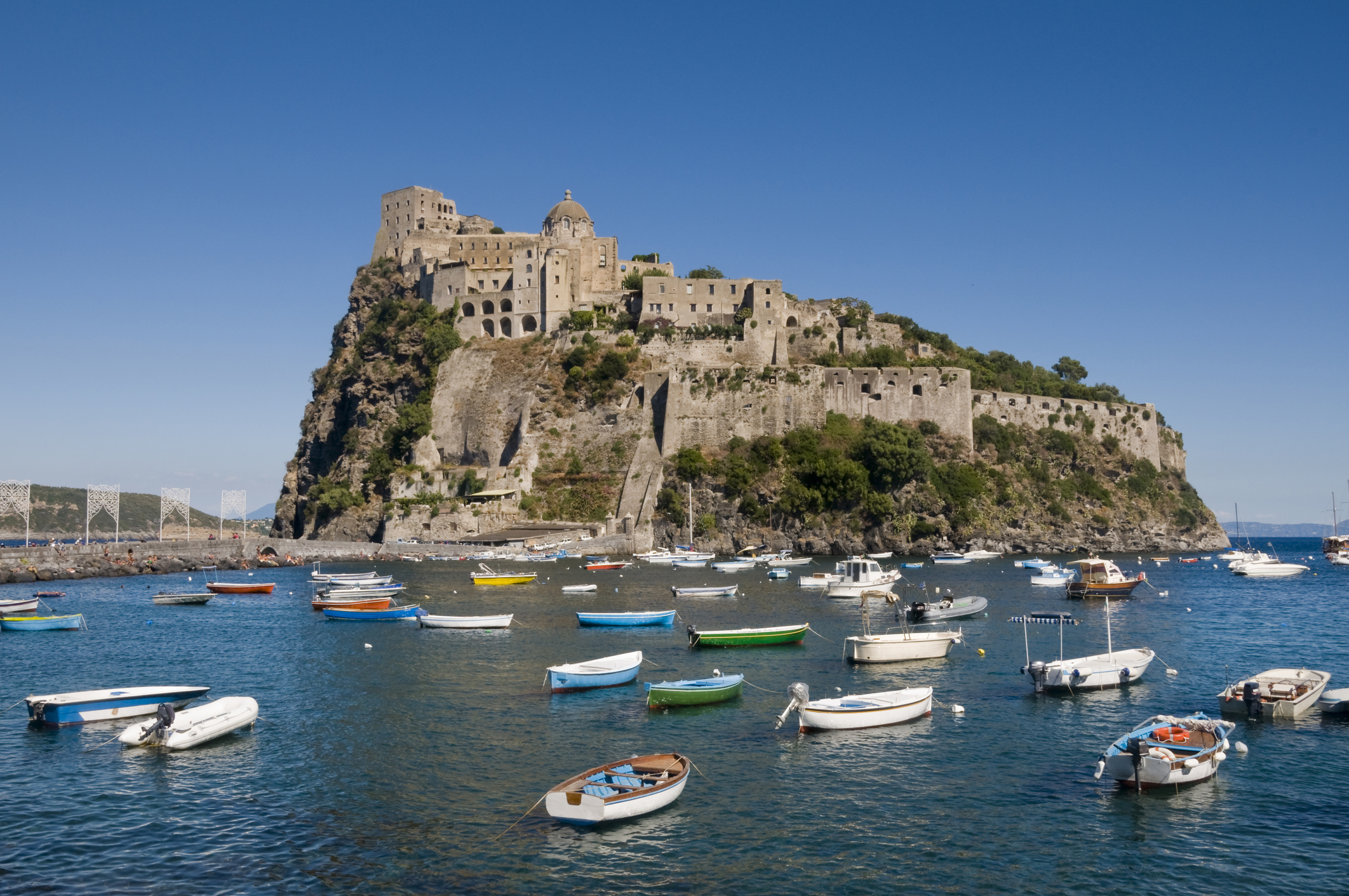 """Castello Aragonese in Ischia Ponte, on Ischia island near Naples, Italy. Many little boats in the sea."""